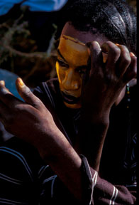 Woodabe tribesman applies paint to his face