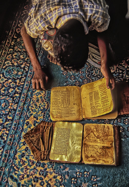 a boy reads the ancient manuscripts of Chinguetti