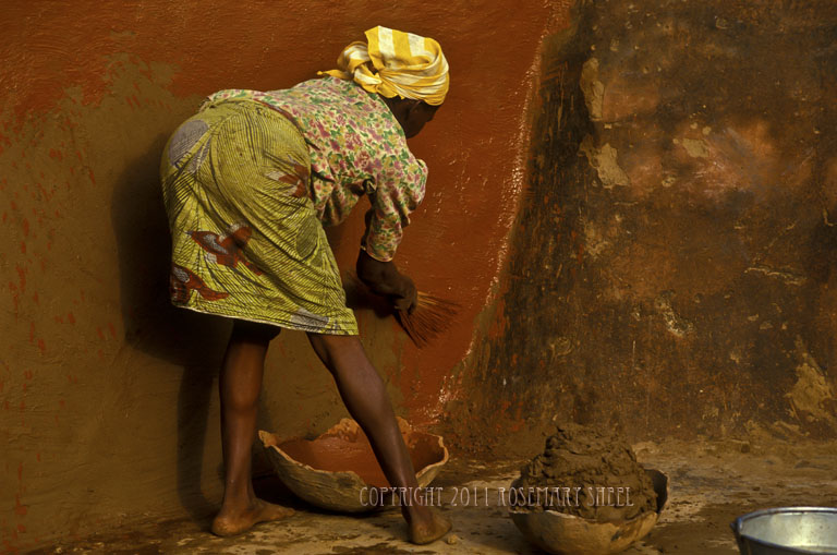 Guerounsi woman painting her house: burkina faso