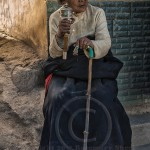 Tibetan woman sits and twirls her prayer wheel in Quinghai Provence China