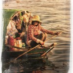 Woman rows her floating shop on Tonle Lake