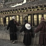 Three Tibetans spin prayer wheels before entering the Monastery