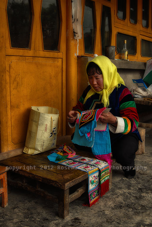 Tibetan woman in Quinghai province, China lays out her needlework