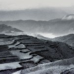 Landscape of China's red earth region with fog rising.