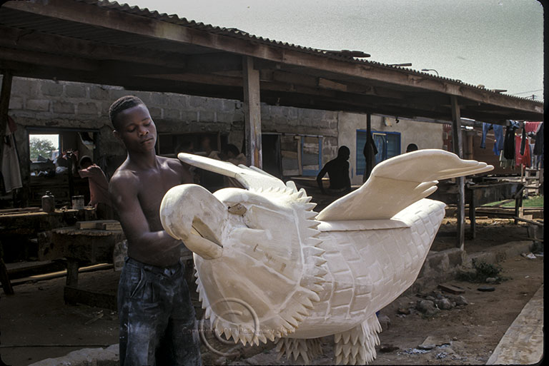 young artist carves a distinctive coffin in Accra Ghana.