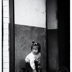 A small Chinese girl sits obediently in a hallway as she keeps an anxious eye out for her mother.