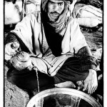 A Berber nomad man sitting in his tent pours tea for guests