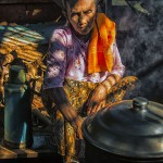 A Burmese village women tends to her steaming cookpot.