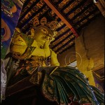 statue of Buddha with halo and dressed in silks on a throne a monastery temple in Ladakh